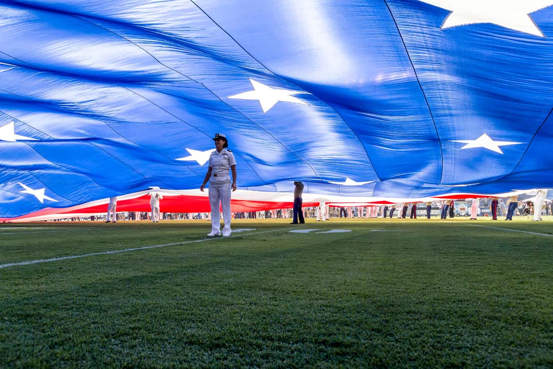 Members of the Armed Forces support the display of the field size America flag. Photo by Bill Reilly