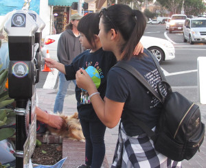 Annie Yang, left, holds on to her mother, Lei Zhant of Vista, as the youngster feeds quarters into a Kindness Meter at the Carlsbad sign last week. Photo by Steve Puterski
