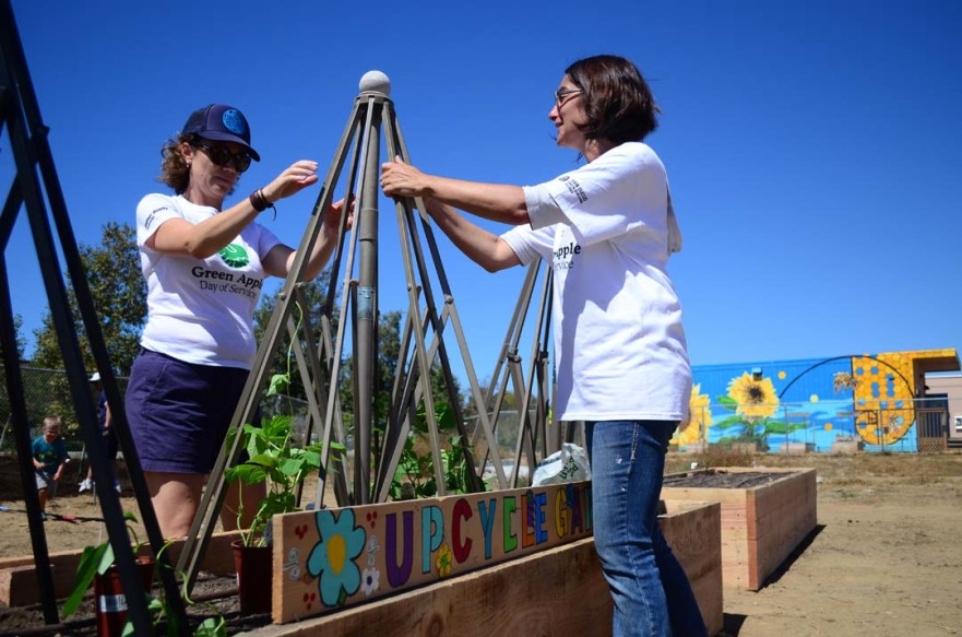 Laura Bier, left, and Mim Michelove, who oversees the farm lab, use old patio umbrellas as trellises in the lab's new upcycle garden beds. Photo by Tony Cagala