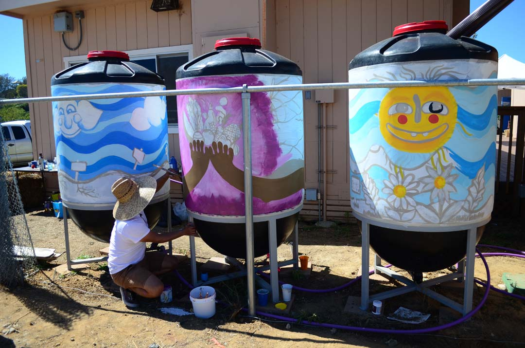 Artist Eddy Berducido helps finish painting one of the rain barrels at the EUSD farm lab. Photo by Tony Cagala
