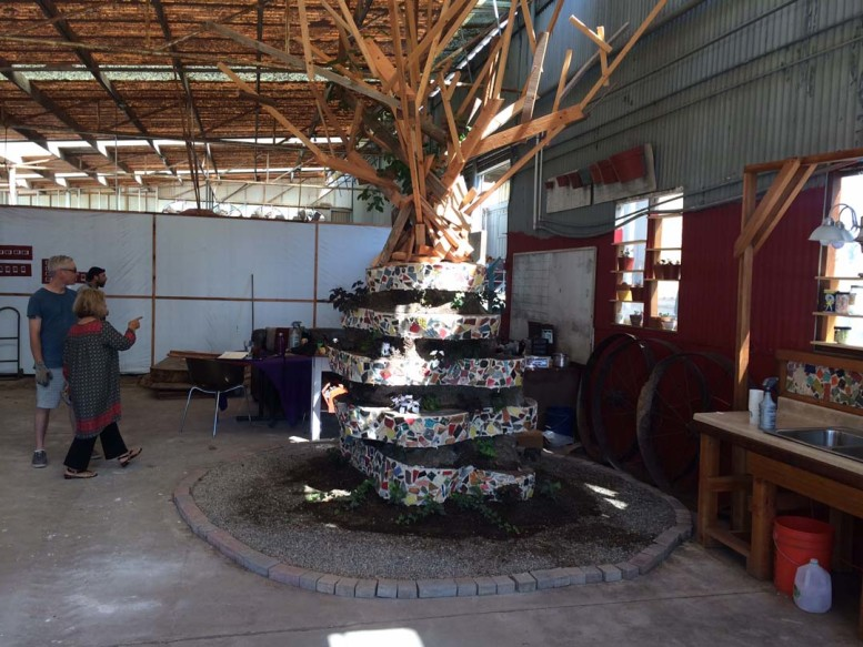 """A tree made of parfait of alternating thin columns of eucalyptus decorated with colorful tiles and fresh earth is the centerpiece of an exhibit at the Leichtag Foundation called the """"Refugee Artists-in-Residence,"""" in Encinitas.  Photo by Aaron Burgin"""
