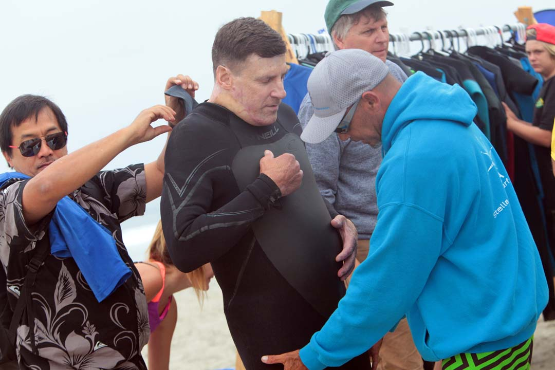 Chris Summers gets some help in putting on his wetsuit as he prepares to take to the water during the Encinitas Lions Club's 21st Annual Blind Surf Event held last Sunday at South Carlsbad State Beach. Photo by Pat Cubel