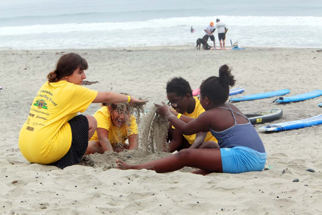 Family members of blind athletes take some time to make new friends and play in the sand. Photo by Pat Cubel