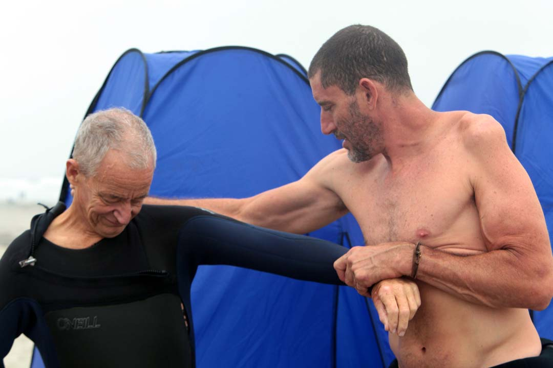 Dominick Manzi gets some help in putting on his wetsuit as he prepares to take to the water. Photo by Pat Cubel