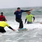 Blind surfer Chris Sommers goes for the stand-up during last Sunday's Encinitas Lions Club's Blind Surfing Event held at South Carlsbad State Beach. Photo by Pat Cubel