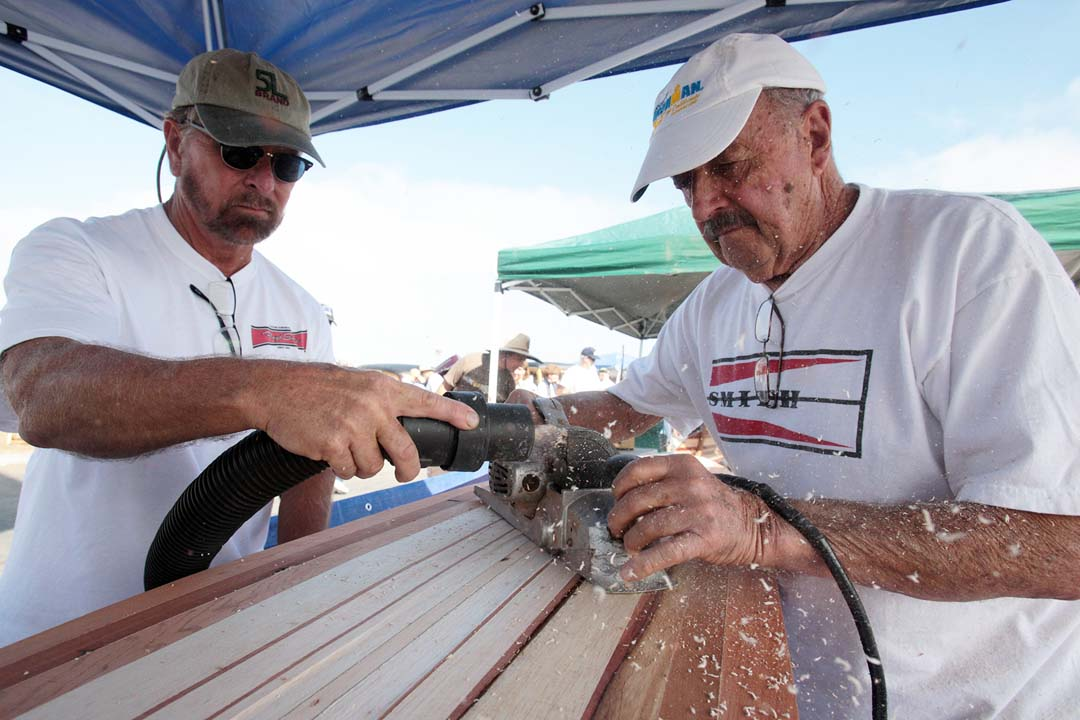 Robbie Jeremicah and master surf board shaper Floyd Smith demonstrate part of Smith's technique.