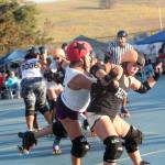 Juan Tu Punch takes an elbow as she tries to pass a member of the Knockouts in roller derby action last Saturday at MLK Park in Oceanside.