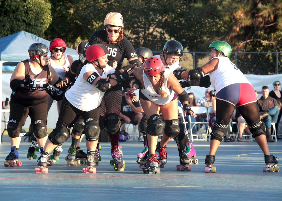The Knockouts, Red Growl Her tries to push her way past to blockers to score points in the opener of roller derby double header at Oceanside's MLK Park last Saturday.
