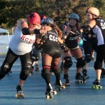 The Sugar Rays jammer, Butterfly Crusher pushes her way around the knockouts blocker in roller derby action last Saturday at Oceanside's MLK Park.