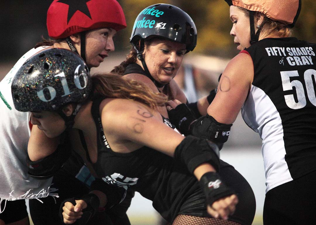 The Knockouts Minalicious puts a shoulder to the chest of Sugar Rays jammer Sidewinder in roller derby action at Oceanside's MLK Park last Saturday.
