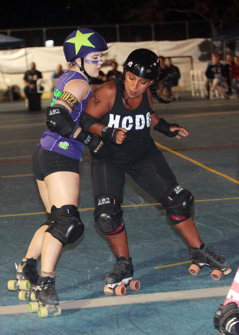 Oceanside's Beachside Bullies, Coo Coo for CoCo throws a shoulder check in to Hartlyn of the San Diego Cuttlefish in roller derby action at Oceanside's MLK Park.