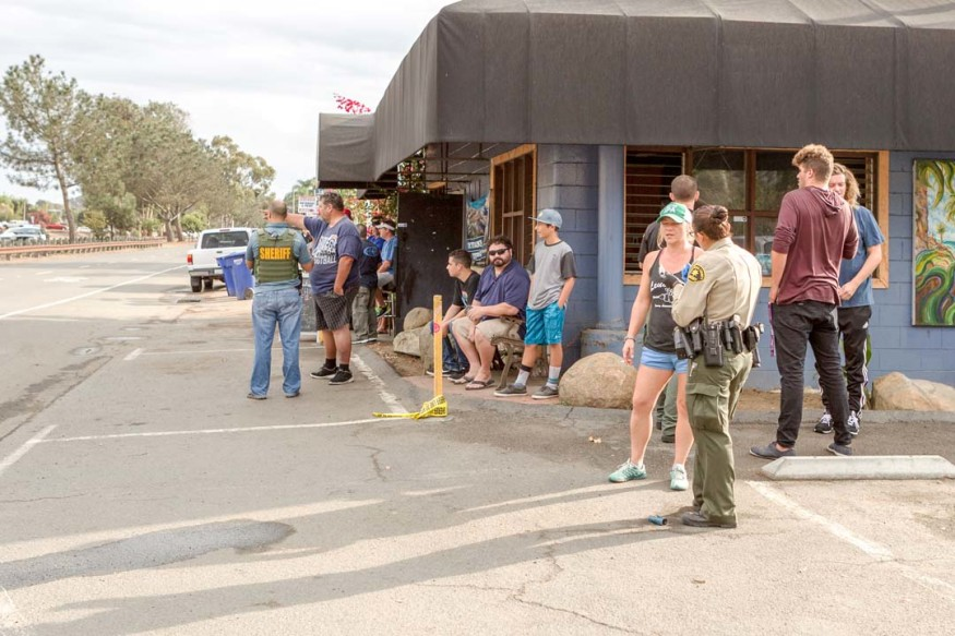 San Diego County Sheriff's deputies interview patrons of Bar Leucadian after an officer involved shooting took place in the 1500 block of North Coast Highway 101 in Leucadia. Photo by Bill Reilly