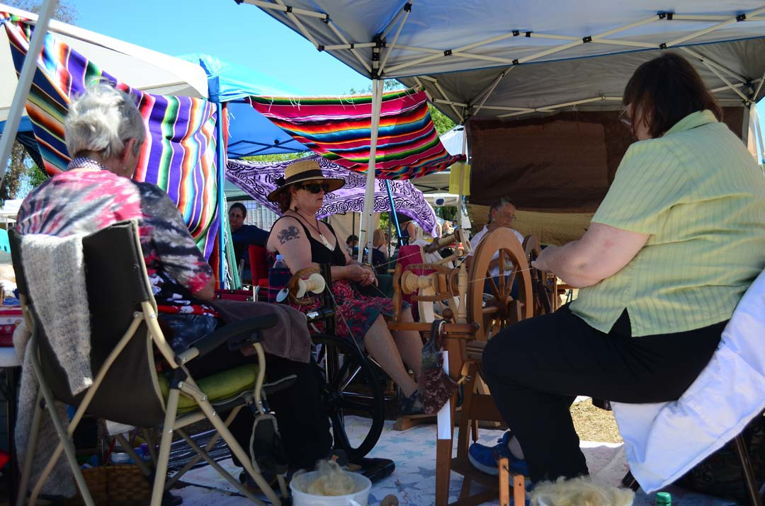 Spinners from the San Diego County Spinners work on spinning and knitting a sweater in a demonstration. Photo by Tony Cagala