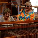 Sharon Gibson, left, with the Palomar Handweavers' Guild shows a festival attendee how a loom works. Photo by Tony Cagala
