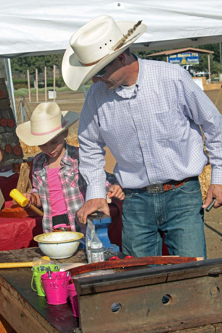 Pat Rowe and his daughter Alise put the finishing touches on some of their leather goods as they prepare for the start of the Horse Heritage Festival last Sunday.  Alise and her sister Lauren are the owners of the business and set up, sell and teach others how to work on and create leather products. Photo by Pat Cubel