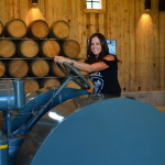 Carrie Peltzer, whose husband's family are fourth-generation farmers, sits on a 1926 tractor purchased by her husband's grandfather. Peltzer designed this wine-tasting room and event space at Peltzer Farms to reflect the family's farm heritage.