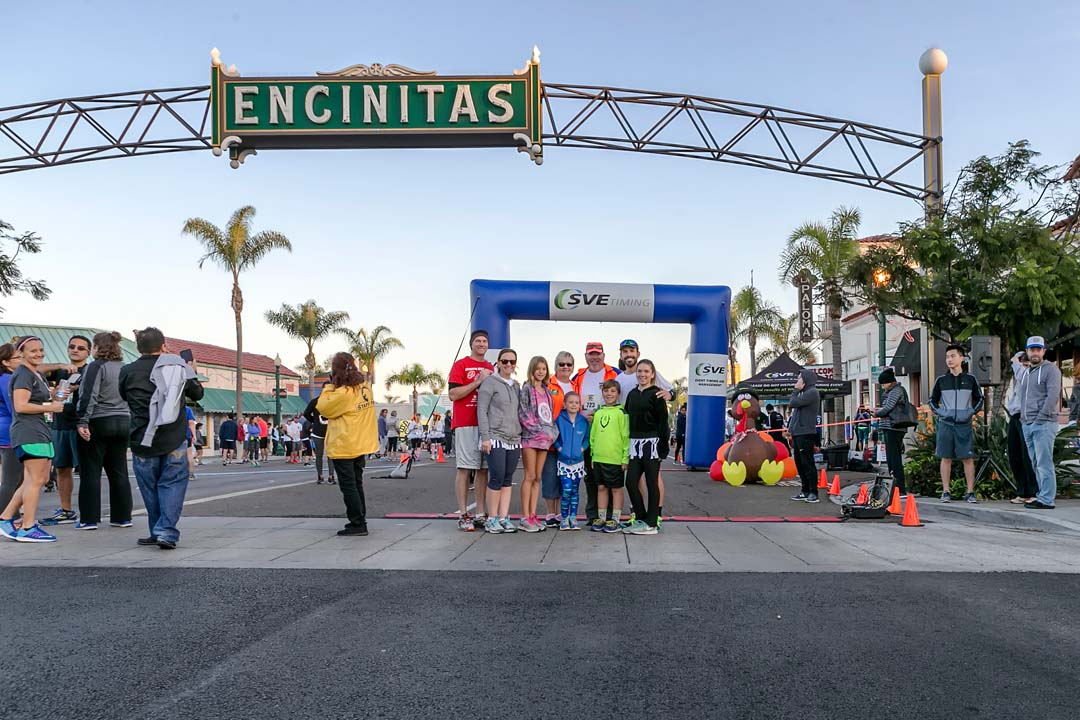 A group of race participants take time for a photo under the famous Encinitas sign before the start of the Encinitas Turkey Trot 10k run on Thanksgiving Day. Photo by Bill Reilly