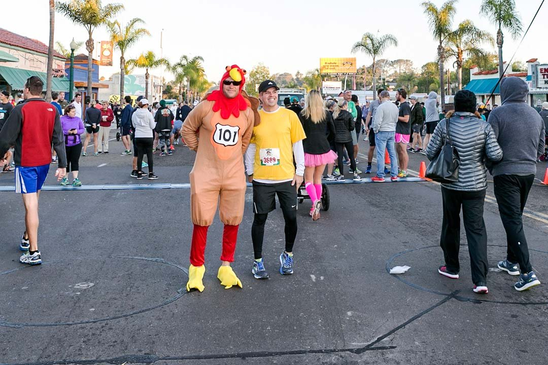 Ed Potts, right, stops to take a photo with race mascot Tom the Turkey before the start of the Encinitas Turkey Trot 10k on Thanksgiving Day. Photo by Bill Reilly