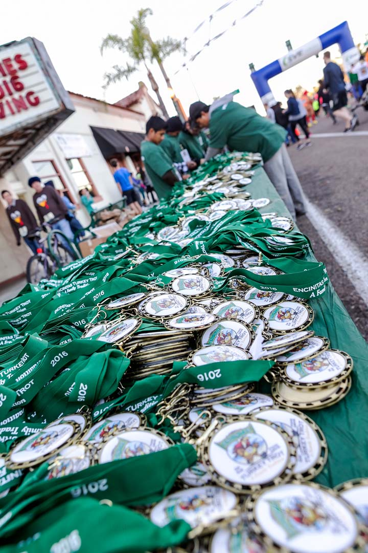Race volunteers lay out medals for all of the participants that took part in the Encinitas Turkey Trot and Food Drive 10k and 5k races on Thanksgiving Day. Photo by Bill Reilly