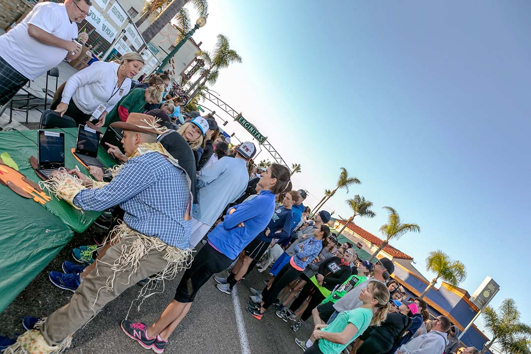 Encinitas Turkey Trot and Food Drive race participants wait in line for race day registration. Photo by Bill Reilly