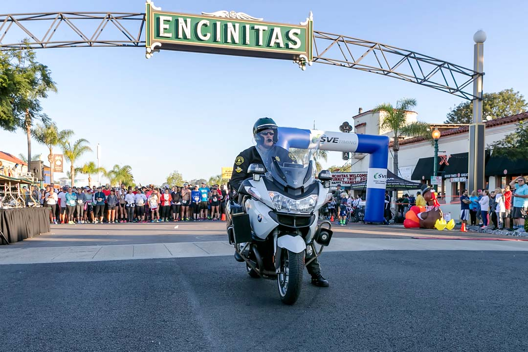 A San Diego County Sheriff's motorcycle officer waits for the start of the 10k run during the Encinitas Turkey Trot and Food Drive event. Photo by Bill Reilly