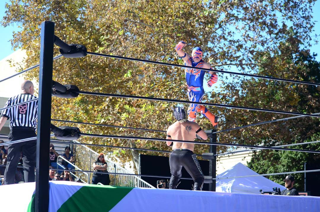 Lucha Underground wrestler Aerostar attempts an aerial maneuver against his opponent Drago during a lucha libre match. Photo by Tony Cagala
