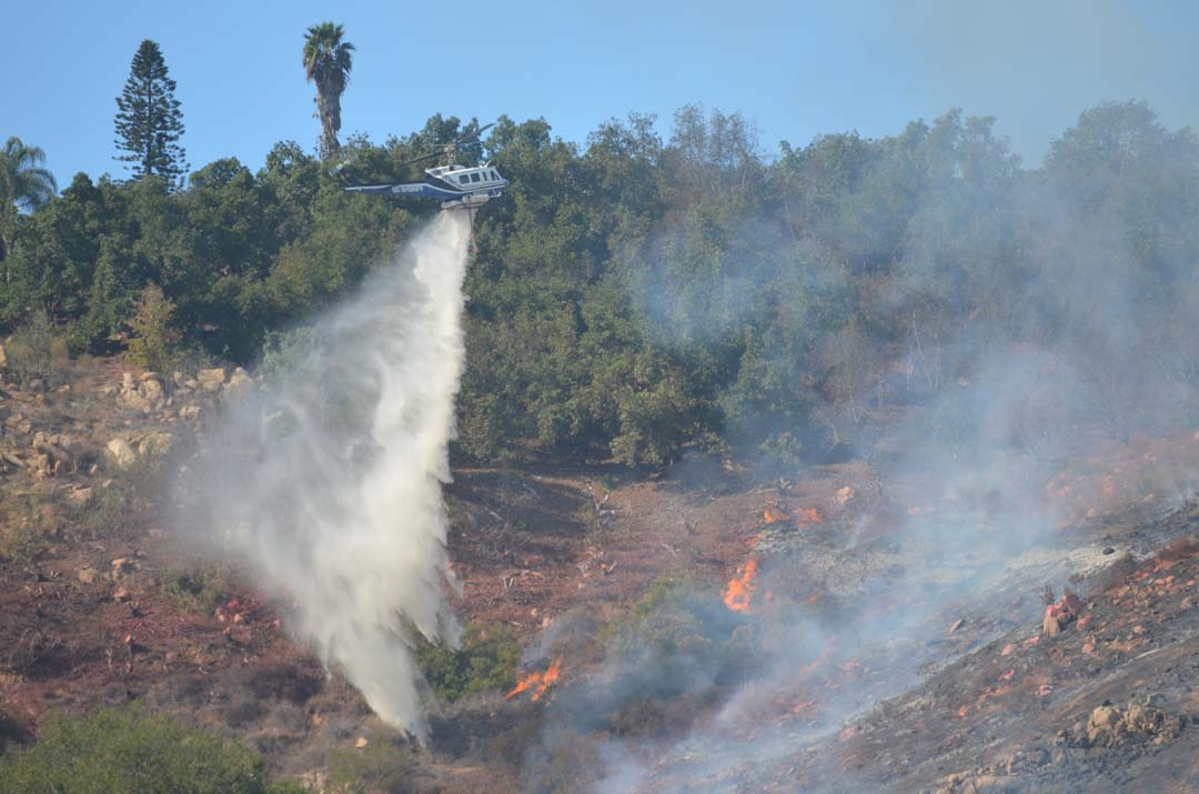 The Gopher Fire is burning at least 15 acres and is about 5 percent contained, according to Cal Fire, as a Sheriff's helicopter drops water on flames. Photo by Tony Cagala