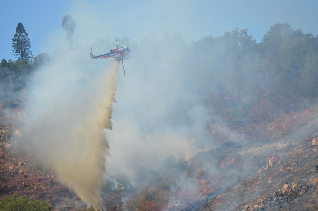 A Cal Fire water-dropping helicopter helps to control a brush fire on Sunday afternoon. Photo by Tony Cagala