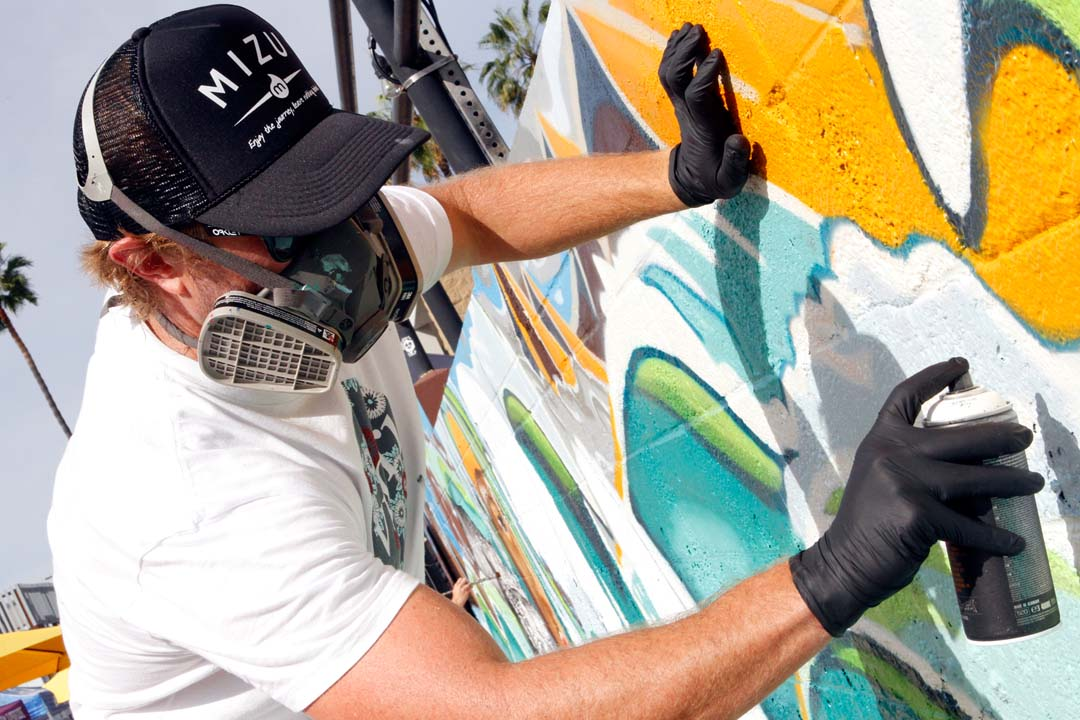 Skye Walker adds finishing touches to his artwork at last Saturday's Cardiff Surf Classic Block Party.  Walker was commissioned by the Cardiff 101 MainStreet organization to paint a mural. Photo by Pat Cubel