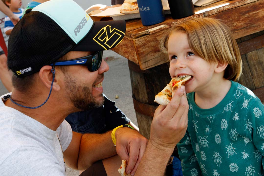 Jose Gonzalez feeds a slice of pizza to his son Leo. Photo by Pat Cubel