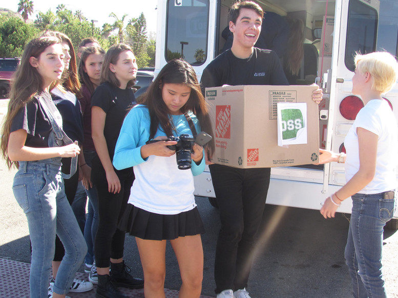 Pacific Ridge School junior David Wiesley unloads boxes of school supplies in Vista on Tuesday from his nonprofit Tools Organize Successful Students to donate. Photo by Steve Puterski