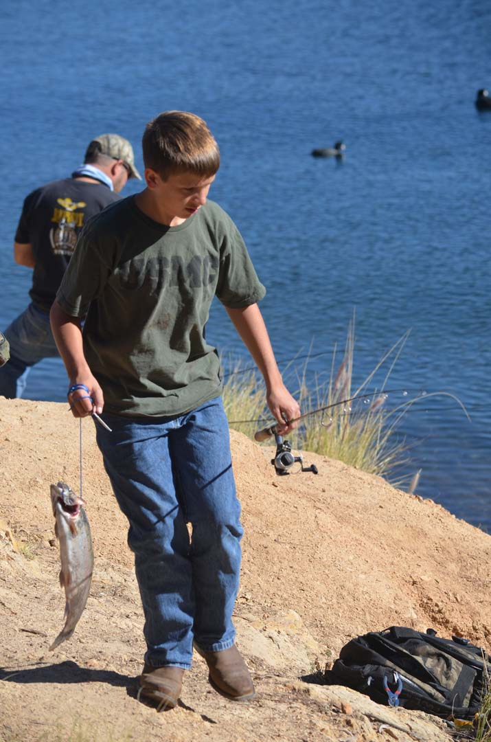 A young angler walks his catch back to the weigh station. Photo by Tony Cagala