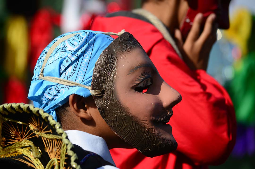 A young performer in mask readies to take to the stage. Photo by Tony Cagala