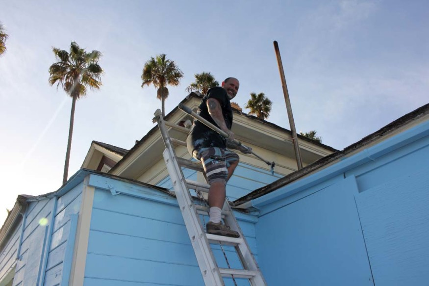 """Painter Larry Keast brushes a fresh coat of blue paint on the """"Top Gun"""" house after complaints about it color. The Queen Anne Victorian was used as a film location in the """"Top Gun"""" movie. Photo by Promise Yee"""