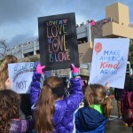 Young girls hold up signs in support of love and kindness. Photo by Tony Cagala