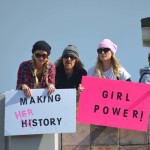 Marchers hold signs in support of women's rights. Photo by Tony Cagala