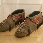 These oldest known existing moccasins are amazingly intact. Made in about 1725 and worn by a Dakota (Eastern Sioux) living in Minnesota, the footwear is fashioned of tanned hide, porcupine quills, red-dyed deer hair, sinew and metal cone. Every stitch and design carries meaning. (Photo by E'Louise Ondash)