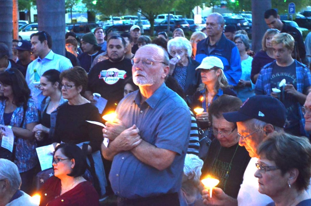 Kevin Kennedy, center, the widower of Catherine Kennedy, is surrounded by support from friends, family and church patrons at a candlelight vigil on Tuesday night. Photo by Tony Cagala