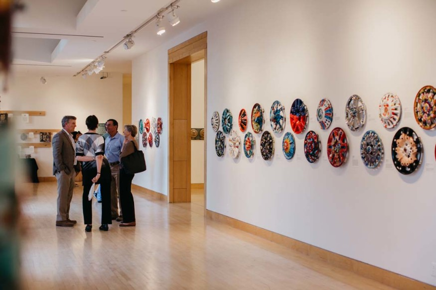 Repurposed hubcaps hang on the wall that make up the Second Time Around exhibit.  Photo by Honey Photographs by Alyss