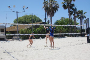 Using the club's new sand courts, former WAVE players Iya Lindahl and Nicole Anderson get ready to score on Coach Juliana Evans. Photo by Bianca Kaplanek