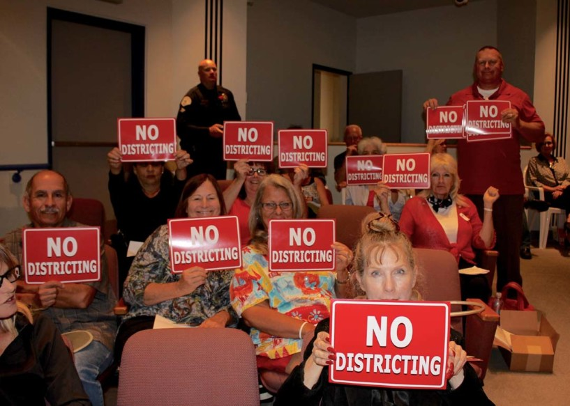 About 50 people held signs in protest of district elections at the May 3 City Council meeting. The council voted for election changes. Photo by Promise Yee