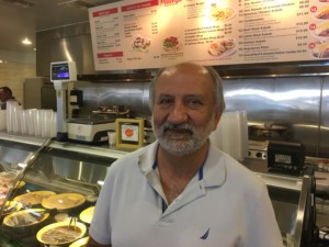 Owner Amir Movassat in front of the delicious grill section of the new Peachy's Market & Grill. Photo David Boylan