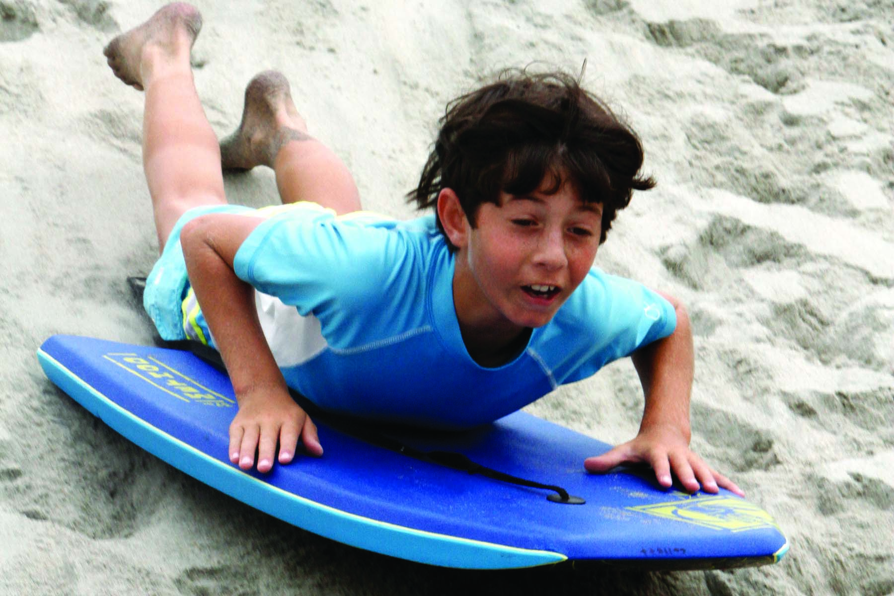 Connor Collets, 10, of Carlsbad, bodyboards down one of the sand dunes at Moonlight Beach. Photo by Pat Cubel