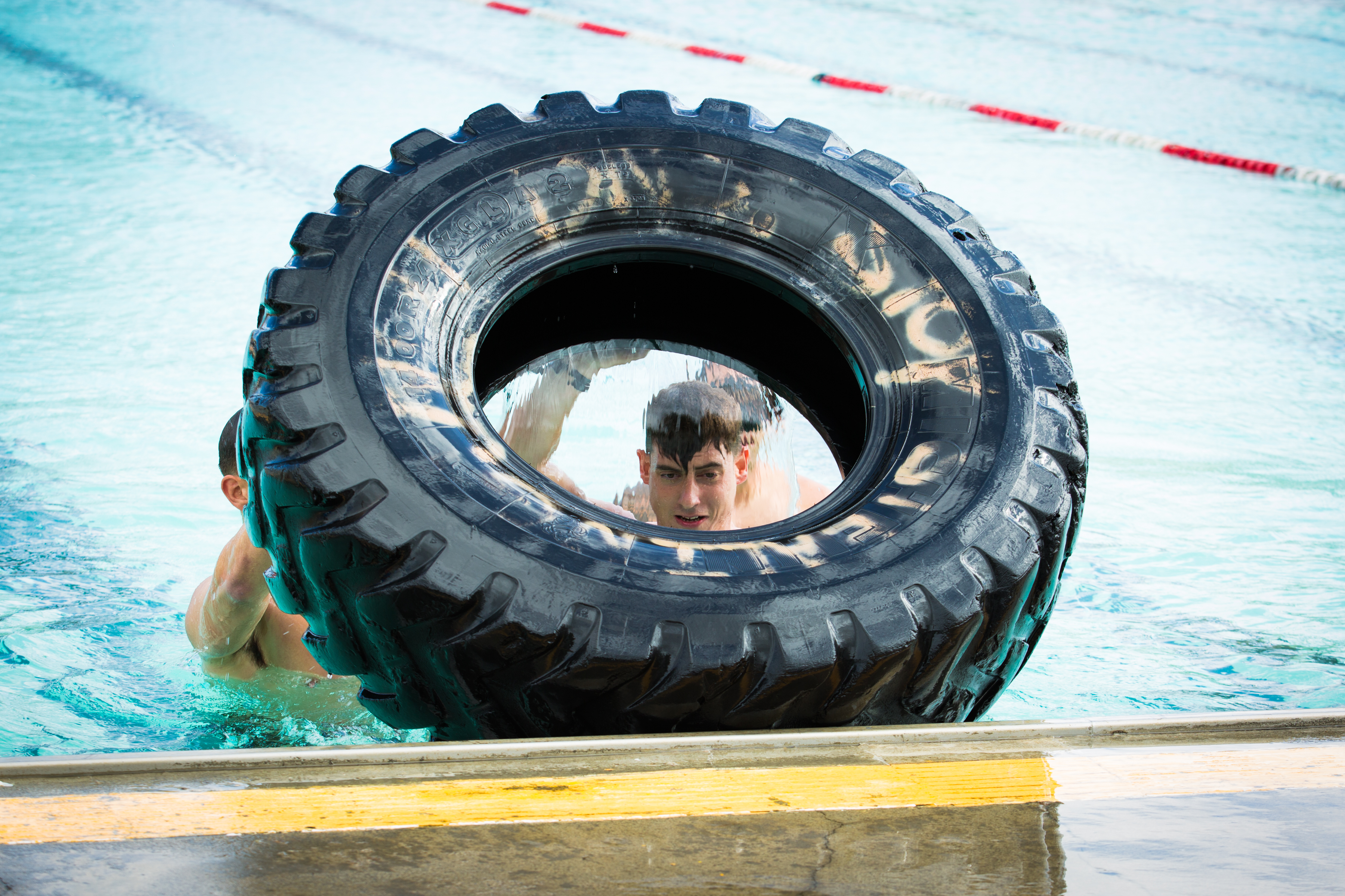 Sgt. Timothy Perez pushes a tire toward his teammate during the Recon Challenge Thursday at Camp Pendleton.