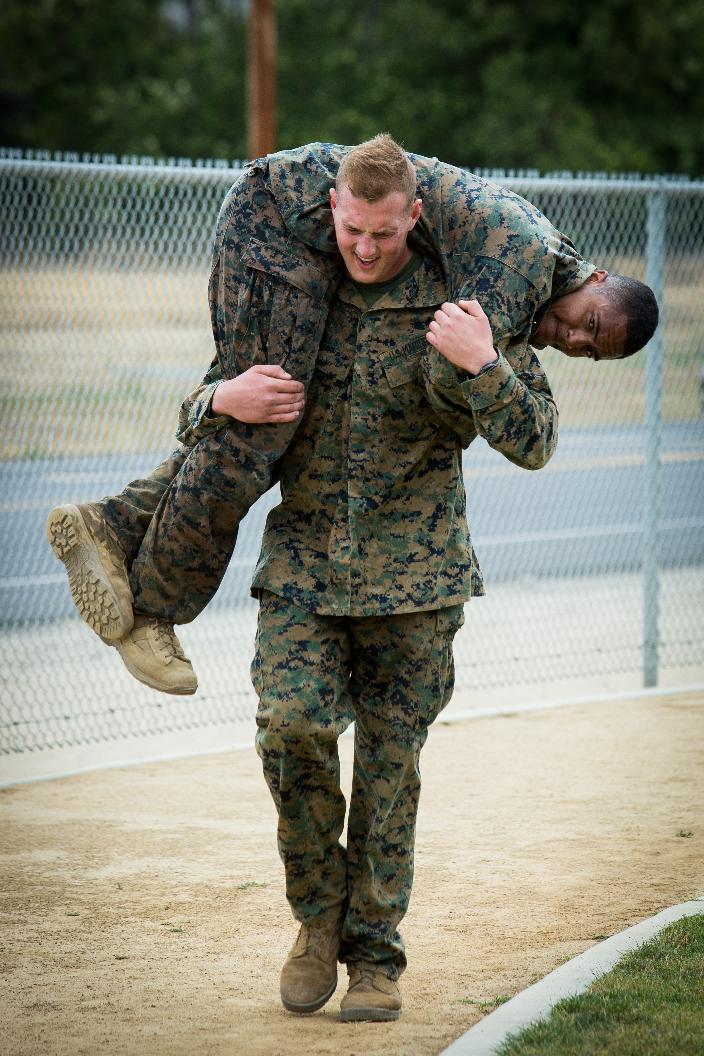2nd Lt. Bradford Mills combat carries his teammate Sgt. Raul Elikahi in honor of their fallen brother Major Douglas Zembiec Thursday at Camp Pendleton.