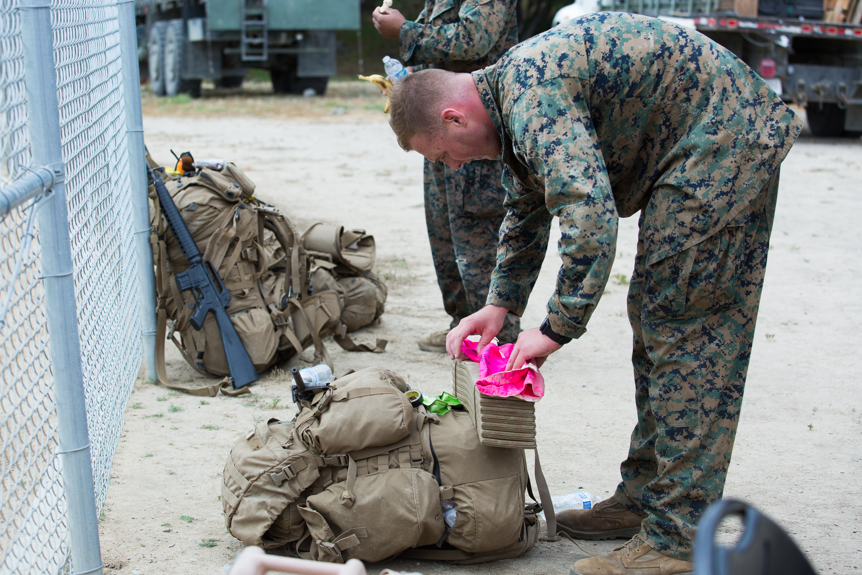 2nd Lt. Bradford Mills folds the pink flag on which the name of his fallen brother is written. He carries the name of Major Douglas Zembiec on his back in memory of his brother as he completes the Recon Challenge Thursday at Camp Pendleton.