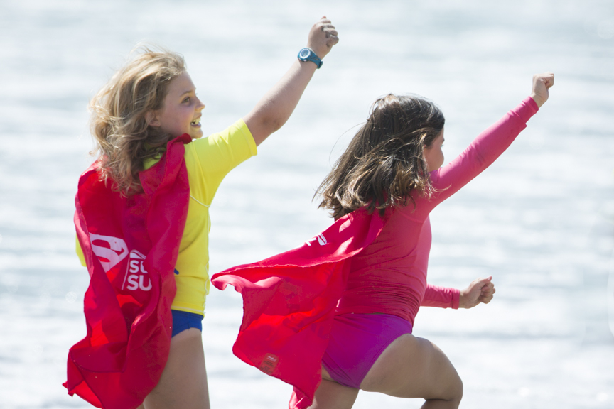 Little Supergirls run down the beach wearing Supergirl capes during the Paul Mitchell Supergirl Pro Sunday in Oceanside.