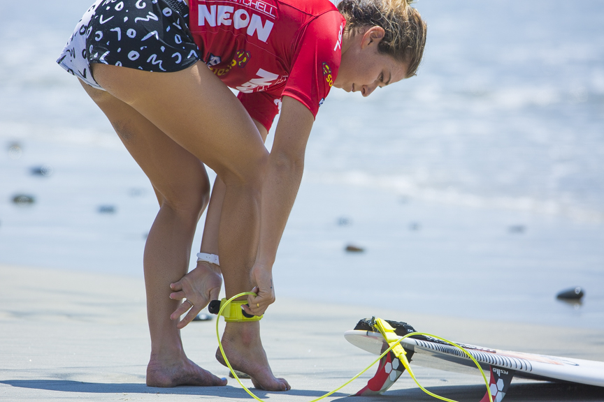 Coco Ho straps on her board as her heat is about to begin in the Paul Mitchell Supergirl Pro Sunday in Oceanside.