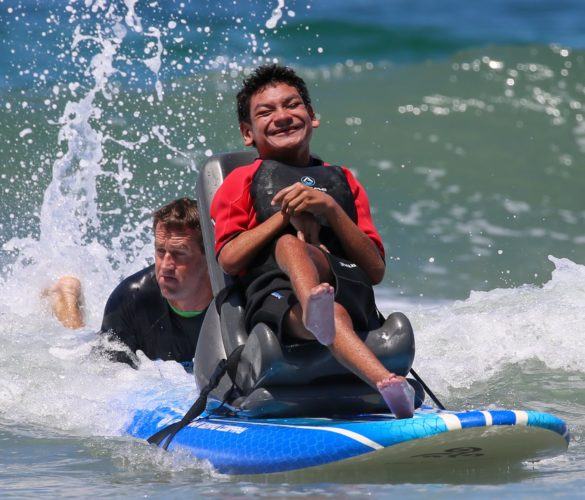Robert Nichols surfs behind Jonah Guerrero on an adaptive surfboard donated by the Kayla Mosca Foundation by Vista's Jennifer and John Mosca.  Photo courtesy Tom Mills