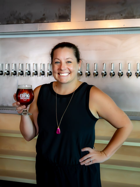 Stephanie Eppig, one of the four founders of Eppig Brewing, celebrates the opening of their new Vista brewery. The brewery is named for her family, which ran a major brewery in Brooklyn from the mid-19th century to the start of Prohibiition. Photo by Bill Vanderburgh.